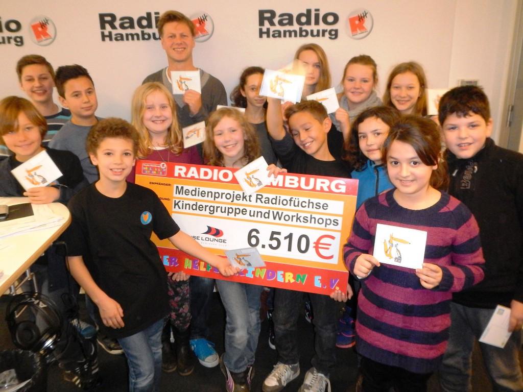 """Scheck-Übergabe bei Radio Hamburg: Die Aktion """"Hörer helfen Kindern"""" unterstützt die Radiofüchse"""